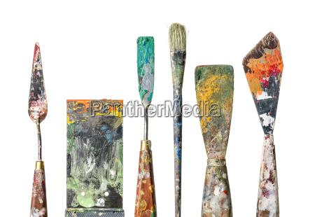 varias espatulas de pintura y pinceles