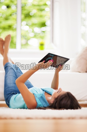 woman using digital tablet at home