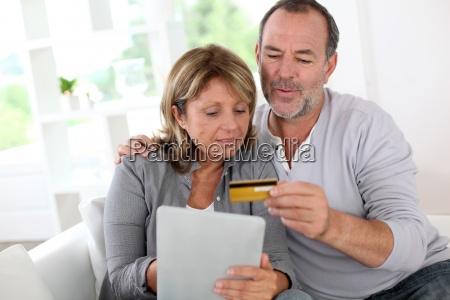 senior pareja con tarjeta de credito