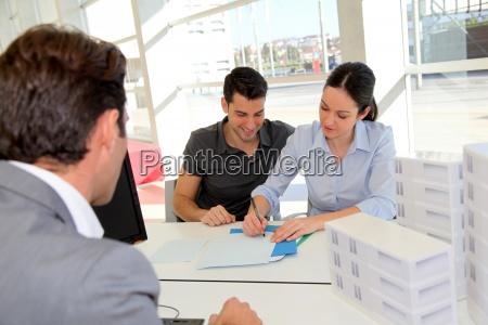 pareja en agencia inmobiliaria firmando contrato