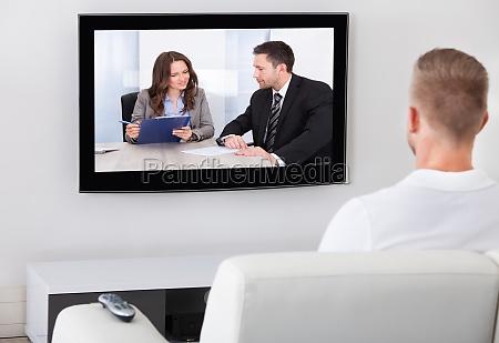 hombre sentado viendo la television en