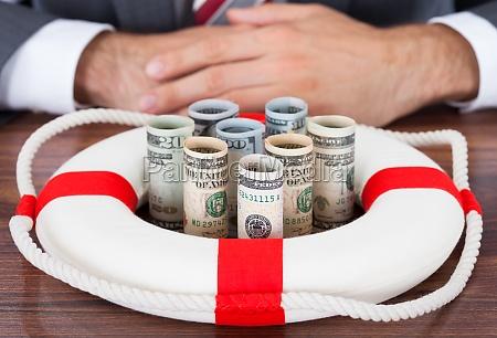 empresario protegiendo billetes de banco enrollado