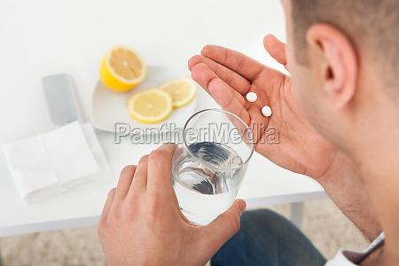 hombre enfermo tomando comprimidos con vaso