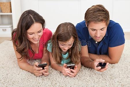 familia usando telefonos inteligentes en el