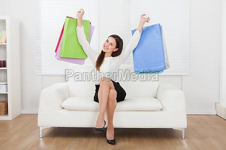 emocionada businesswoman sosteniendo bolsas de compras