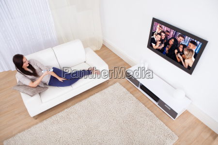 mujer viendo la television mientras se