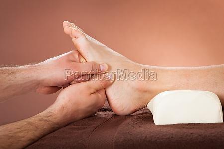 terapeuta que da masaje de pies