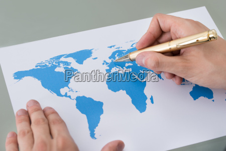 businessman marking places on world map