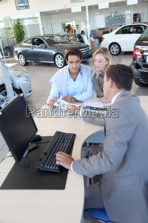 car seller and couple looking at