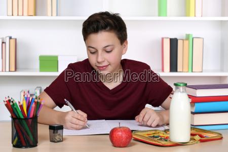 boy writing homework at school