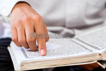 hombre asiatico musulman estudiando coran o