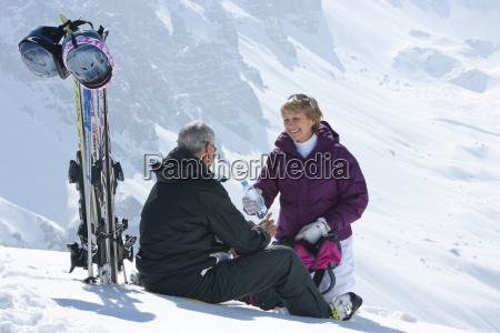 senior couple with skis and water