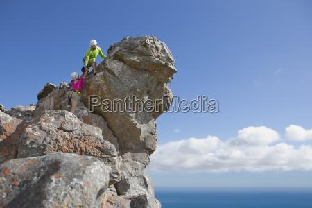 hombre escalador de roca ayuda a