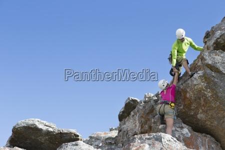 trepadora de roca masculina ayudando a