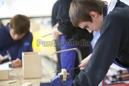 boy con sierra para cortar madera