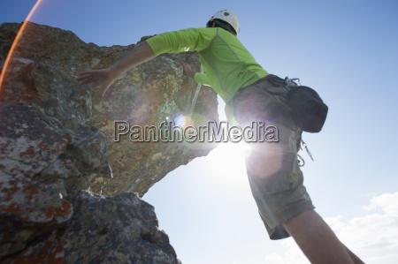 sol que brilla detras hombre escalador