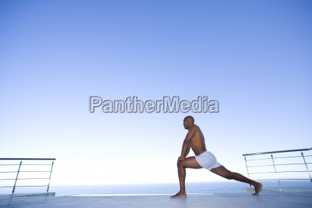 young man stretching legs by sea