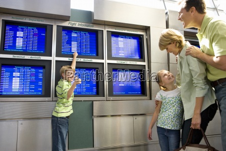 family standing in airport departure lounge