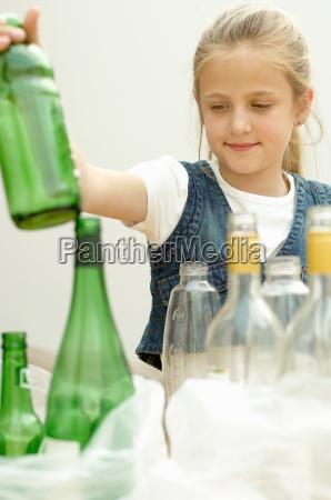 chica que separa la botella de