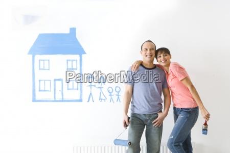pareja sonriente junto a la casa