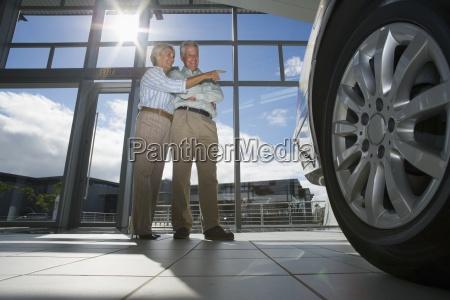 senior couple standing in car showroom