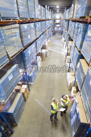 warehouse workers with clipboard looking up