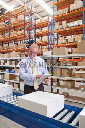 supervisor with digital tablet examining boxes