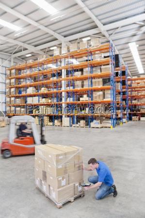 worker scanning cardboard boxes on pallet