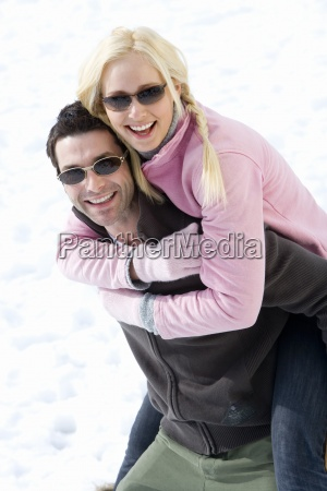 young couple wearing sunglasses in snow