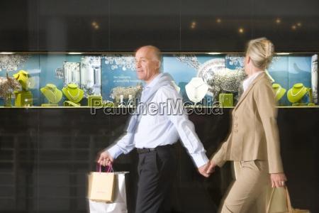 mature couple walking past jewelery store