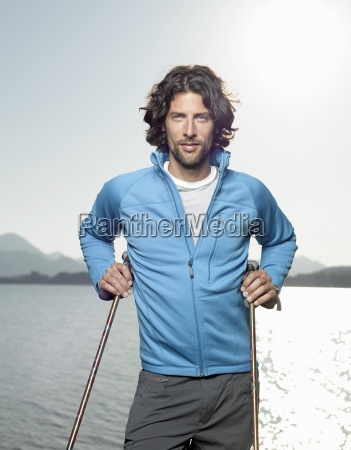a young man beside a lake