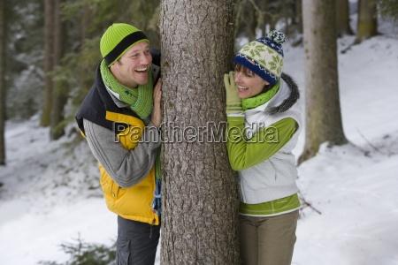 sonriente pareja apoyada contra el tronco
