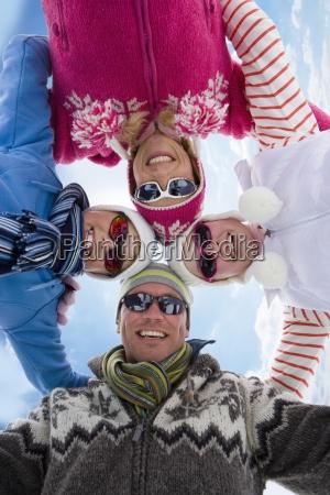 familia sonriente abrazando en circulo junto