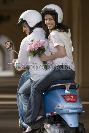couple riding on motor scooter near