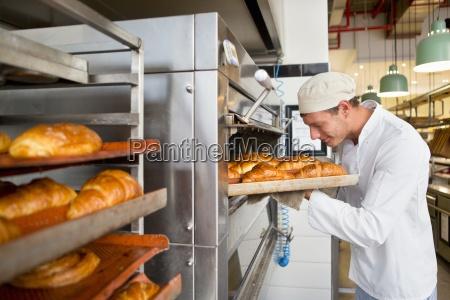 panadero sonriente que controla la bandeja