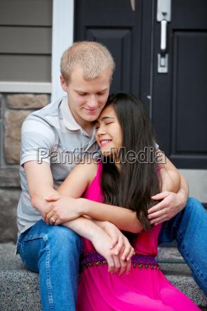joven feliz pareja diversa sentados juntos
