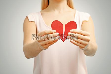 roto el corazon rojo en manos