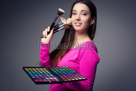 cute maquillaje artista sosteniendo su amplia
