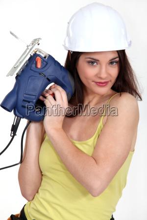 foxy hembra carpintero sosteniendo maquina lijadora