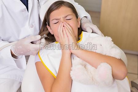 dentista pediatrico tratando de ver estornudos