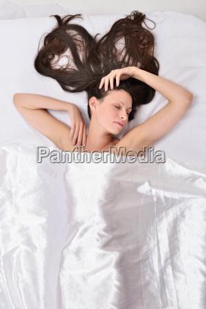 mujer hermosa en la cama debajo