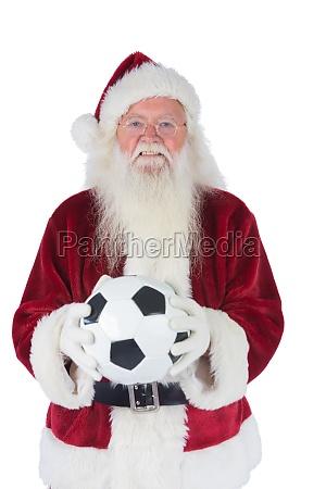 santa sostiene un balon de futbol