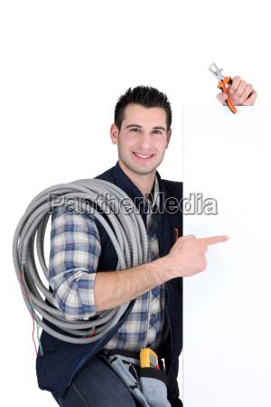 electricista parado por el tablero de