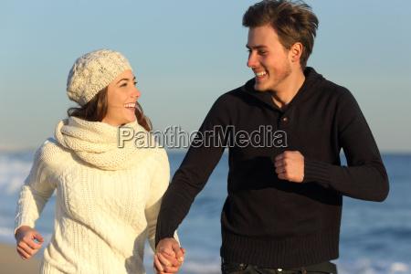 pareja corriendo en la playa en