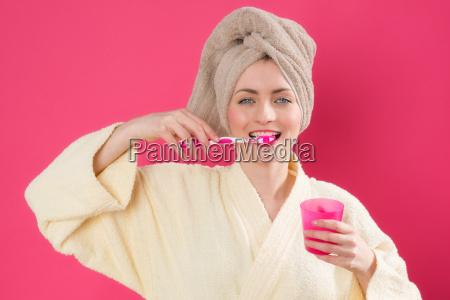 woman in bathrobe brushing her teeth