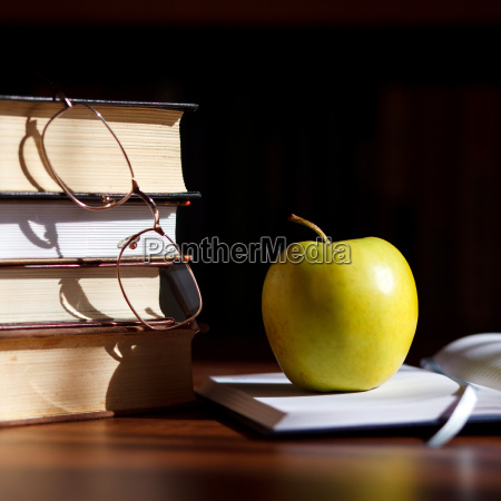 green apple on the open book
