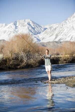 young woman fly fishing with mountains