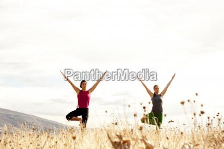 dos mujeres que practican yoga al