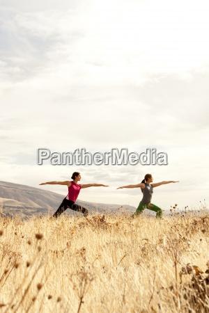 dos hembras practicando yoga al aire