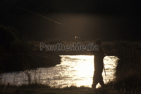 a man in waders cast his